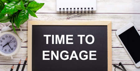 TIME TO ENGAGE written on a black background near pencils, a smartphone, a white notepad and a green plant in a pot
