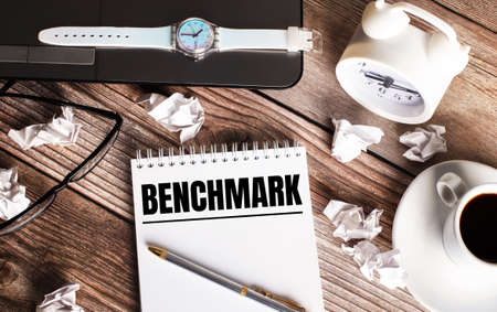 There is a cup of coffee on a wooden table, a clock, glasses and a notebook with the word BENCHMARK. Business concept