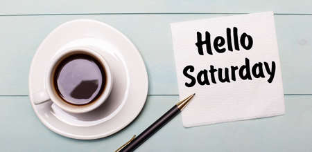 On a light blue wooden tray, there is a white cup of coffee, a handle and a napkin that says HELLO SATURDAY