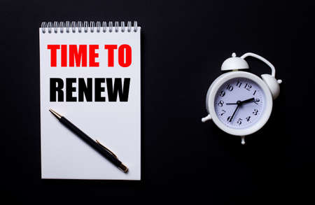 TIME TO RENEW is written in a white notepad near a white alarm clock on a black background.