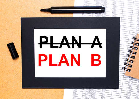 On a wooden table, there is a black open marker, a brown notepad and a sheet of paper in a black frame with the text PLAN B. View from above.
