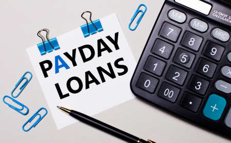 On a light background, a calculator, a pen, blue paper clips and a sheet of paper with the text PAYDAY LOANS. View from above