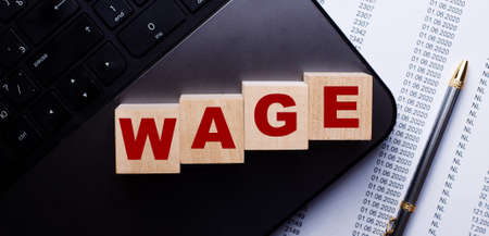 The word WAGE is written on wooden cubes on the keyboard next to the pen.