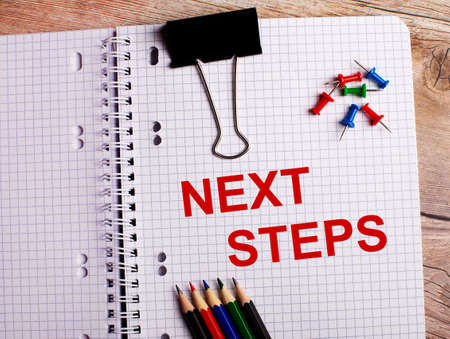 The words NEXT STEPS is written in a notebook near multi-colored pencils and buttons on a wooden background. Foto de archivo