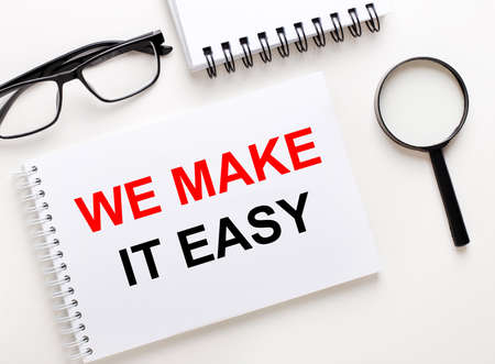 WE MAKE IT EASY is written in a white notebook on a light background near the notebook, black-framed glasses and a magnifying glass. Stock fotó