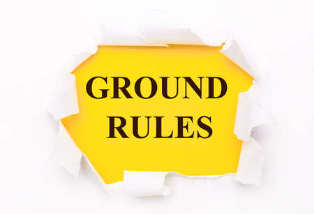 Torn white paper lies on a bright yellow background with the text GROUND RULES