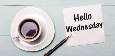 On a light blue wooden tray, there is a white cup of coffee, a handle and a napkin that says HELLO WEDNESDAY