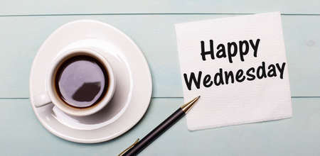 On a light blue wooden tray, there is a white cup of coffee, a handle and a napkin that says HAPPY WEDNESDAY