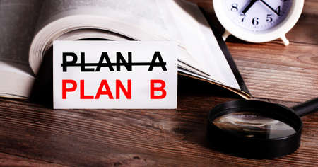 The words PLAN B written on a white card near an open book, alarm clock and magnifying glass