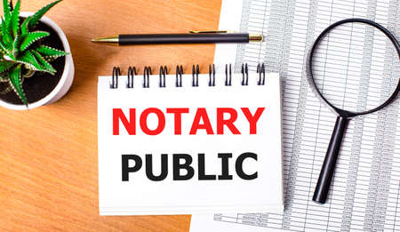 On a wooden table there are reports, a potted plant, a magnifying glass, a black pen and a notebook with the text NOTARY PUBLIC. Business concept