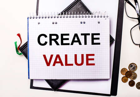 On a light background glasses, coins and a notebook with the inscription CREATE VALUE. Business concept