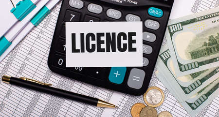 On the desktop are reports, a pen, cash, a calculator and a card with the text LICENCE. Business concept