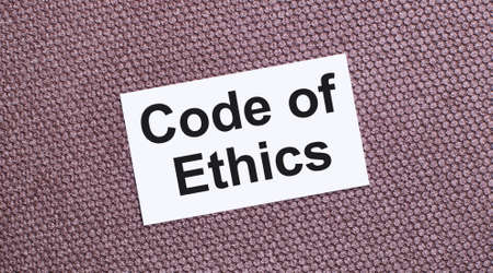 On a brown background, a white rectangular card with the text CODE OF ETHICS Stock Photo