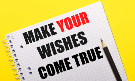 White notebook with inscription MAKE YOUR WISHES COME TRUE written in black pencil on a bright yellow background. Archivio Fotografico