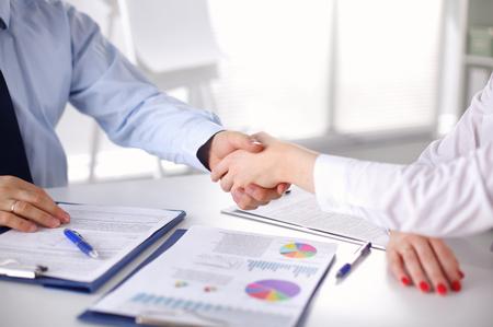 Obchodní lidé handshake, sedí u stolu.