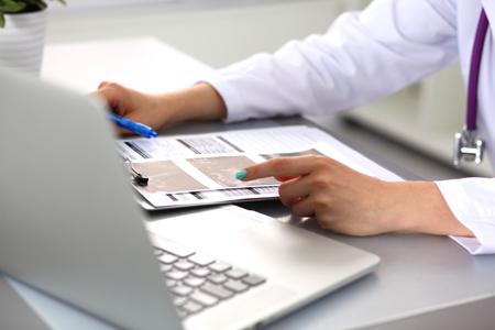 uniformes de oficina: Retrato de mujer joven médico en bata blanca en la computadora.