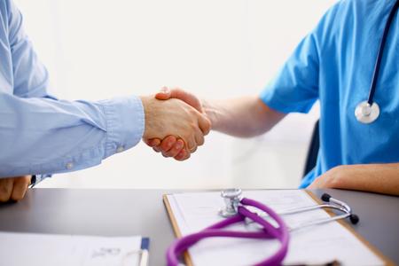 Atraktivní ženský lékař potřásl rukou pacient je ve své kanceláři.