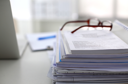 informe: oficina de mesa de una pila de formularios de informes de trabajo de papel ordenador. Foto de archivo
