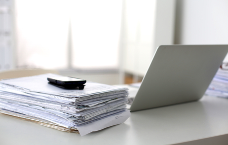 paper stack: office desk a stack of computer paper reports work forms.