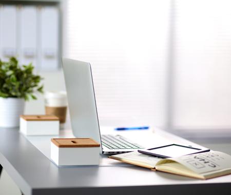 Kancelářský stůl s prázdnou poznámek a notebooku.