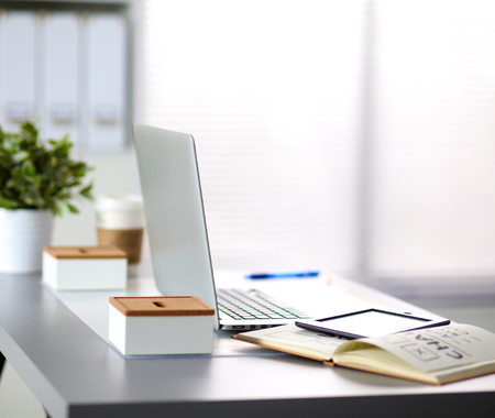 Office table with blank notepad and laptop .