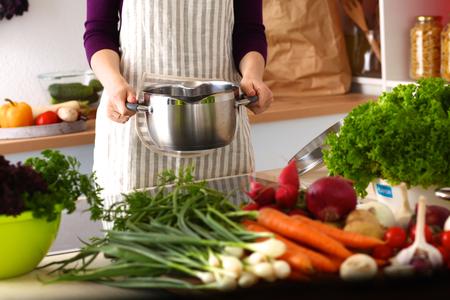 mujeres cocinando: Una chica joven en la cocina mientras se cocina.