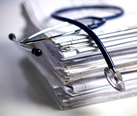 stethoscope: Medical stethoscope rests on a stack of documents. Stock Photo