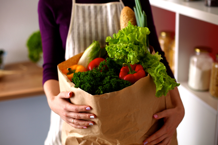 Young woman holding grocery shopping bag with vegetables.