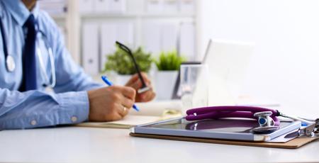 가까운 노트북에 남성 의사 입력의 직장에서 의사. 스톡 콘텐츠