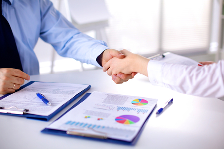 Business meeting at the table shaking hands conclusion of the contract. Banque d'images