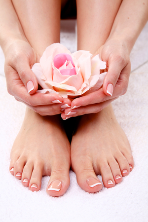 footcare: pedicure on legs and beautiful manicure on hands closeup.