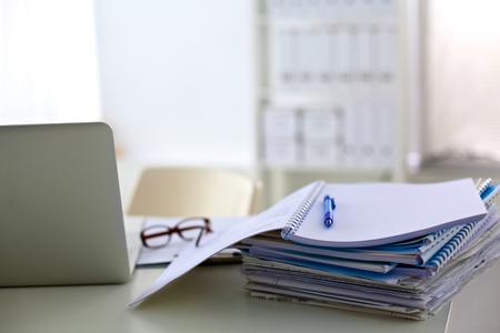 secretaria: una pila de papeles sobre el escritorio con una computadora.