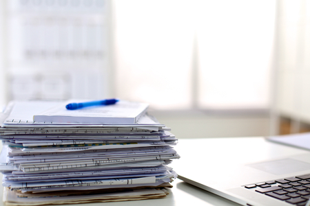 stack of papers: a stack of papers on the desk with a computer.
