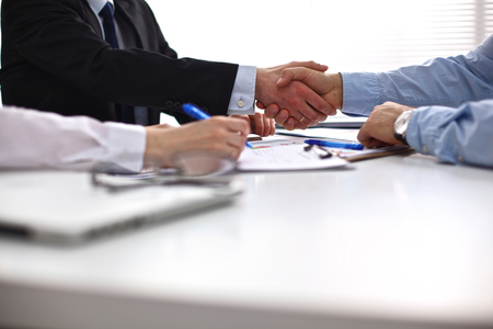 Business meeting at the table shaking hands conclusion of the contract. Фото со стока