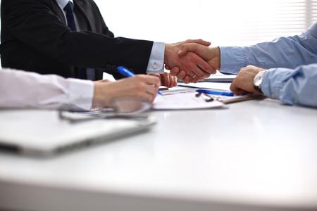 stretta mano: Incontro di lavoro al tavolo si stringono la mano conclusione del contratto.