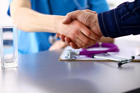 Office uniforms: Doctor con el estetoscopio en el ingreso del paciente en la mesa.