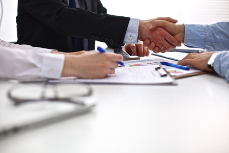 contrato de trabajo: Reunión de negocios en la mesa dando la mano la celebración del contrato.