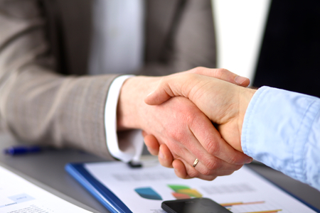 conclusion: Business meeting at the table shaking hands conclusion of the contract. Stock Photo