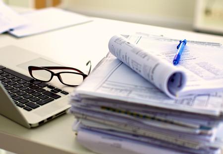 document management: oficina de mesa de una pila de formularios de informes de trabajo de papel ordenador. Foto de archivo