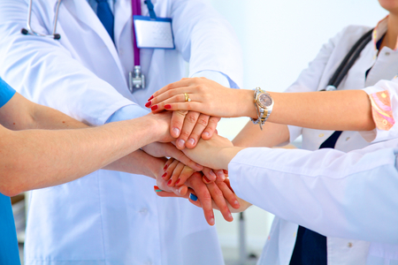 join the team: Group of doctors joining hands with low angle view. Stock Photo