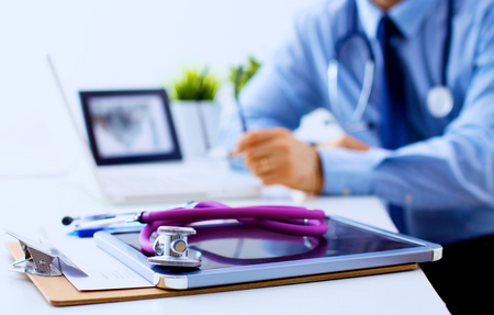 office uniform: Doctor at work, close up of male doctor typing on a laptop.