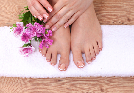 french pedicure: Relaxing pink manicure and pedicure with a orchid flower. Stock Photo