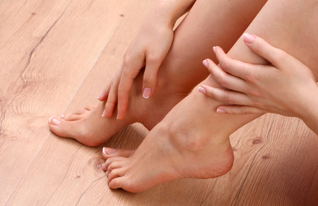 spa treatments: Closeup photo of a beautiful female feet with red pedicure isolated on white.