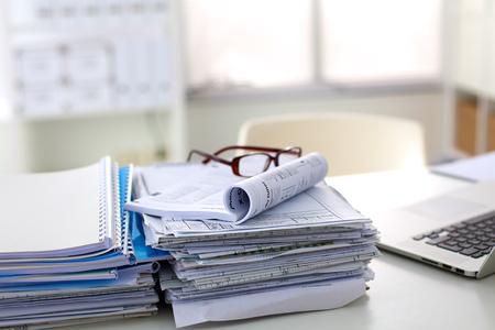 Stapel documenten en glazen liggend op tafel desaturated.