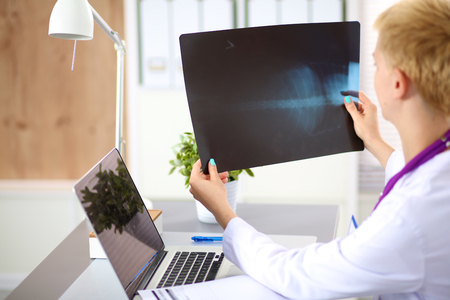 accurately: Confident female doctor examining accurately a rib cage x-ray. Stock Photo