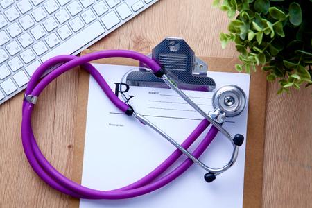 estetoscopio: Un estetoscopio médico cerca de una computadora portátil en una mesa de madera, sobre fondo blanco. Foto de archivo