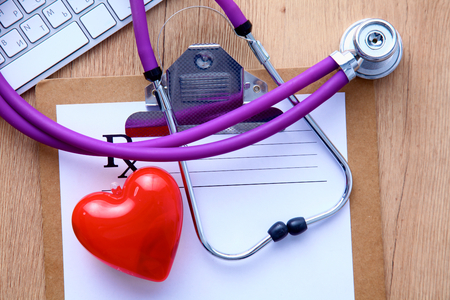 pc monitor: A medical stethoscope near a laptop on a wooden table, on white. Stock Photo