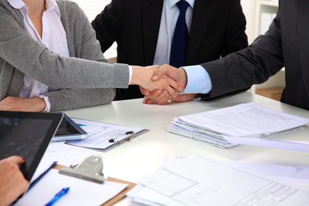 strong message: Business people shaking hands, finishing up a meeting. Stock Photo