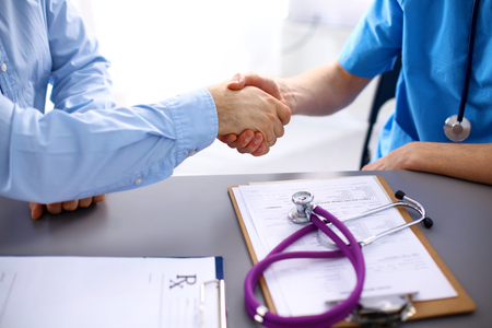 consulting: Female doctor holding application form while consulting patient.