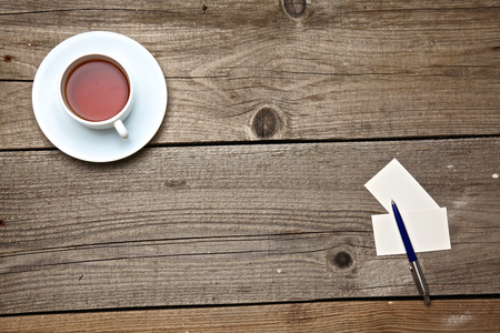 Blank business cards with pen and tea cup on wooden office table. Stock Photo